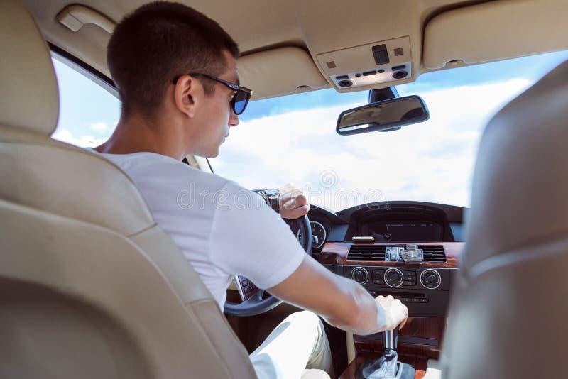 驾驶汽车的太阳镜的年轻时髦的人 从后面的看法,有后坐的乘客位子的 库存照片