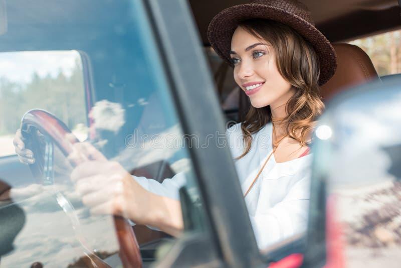 驾驶汽车的帽子的愉快的美丽的年轻女人在期间 库存图片