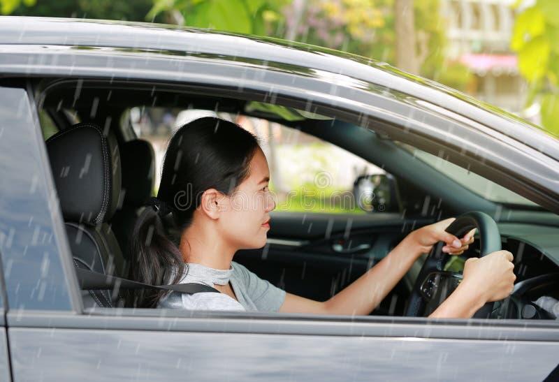 驾驶汽车的年轻亚裔妇女,当下雨时 免版税库存图片