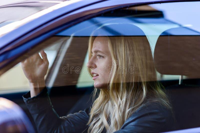 驾驶汽车的年轻沮丧的妇女 免版税库存图片