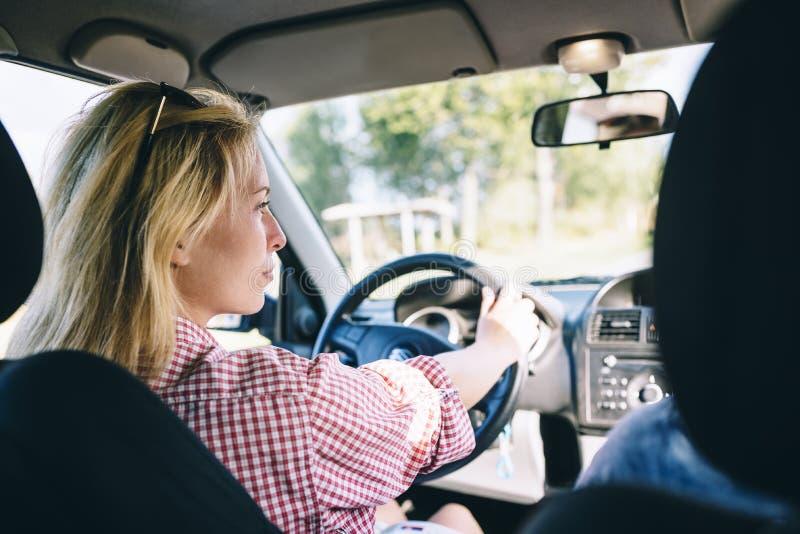 驾驶汽车的年轻白肤金发的妇女 免版税库存照片