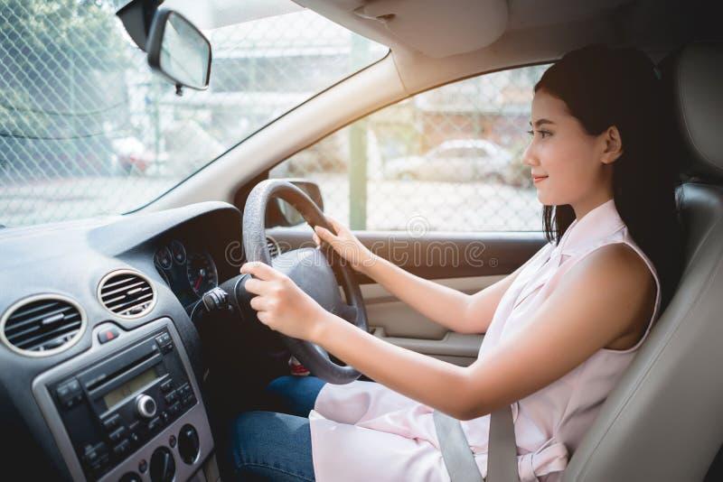 驾驶汽车的年轻美丽的微笑的女孩藏品轮子看直接与游乐器具 驾驶概念的安全 库存照片