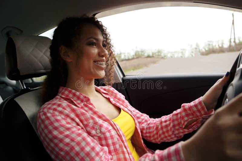 驾驶汽车的年轻美丽的微笑的妇女 她逗人喜爱的女儿坐后方和享用 库存照片