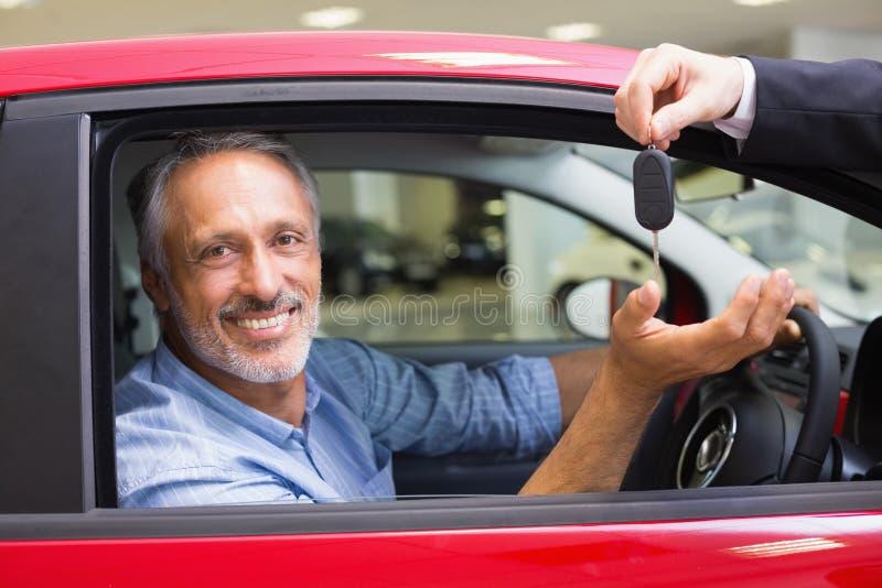 驾驶汽车的微笑的人,当推销员他给的钥匙时 库存图片