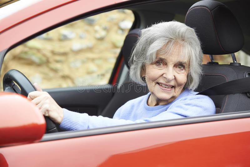驾驶汽车的微笑的资深妇女画象  免版税库存图片