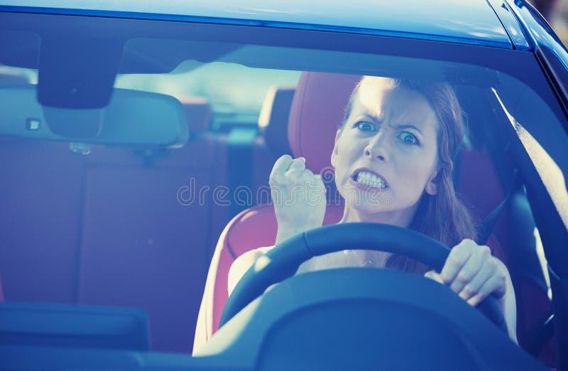 驾驶汽车的恼怒的积极的妇女 库存图片