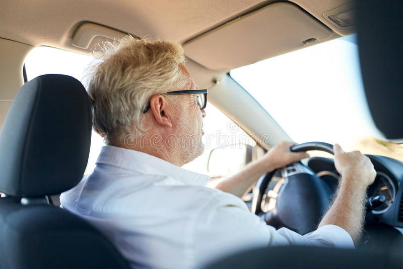 驾驶汽车的愉快的老人 免版税库存照片