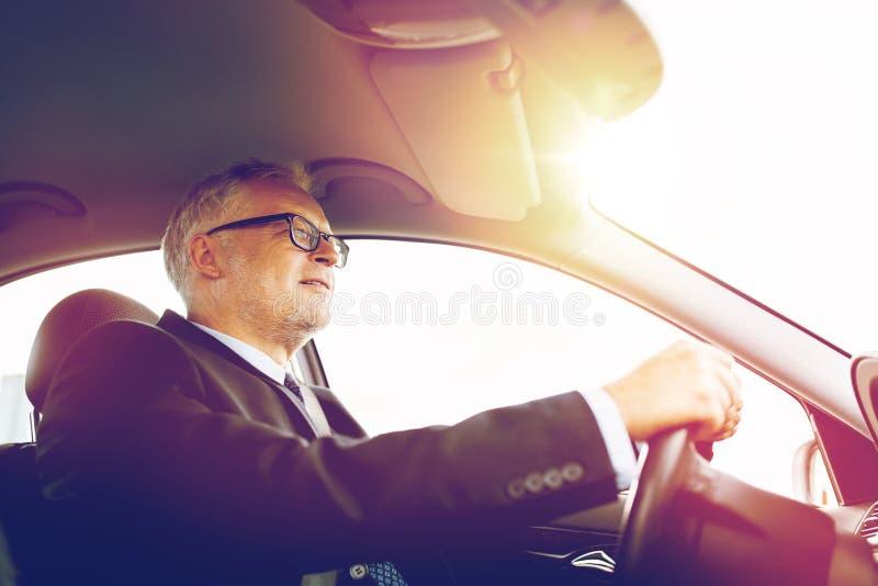 驾驶汽车的愉快的资深商人 免版税图库摄影