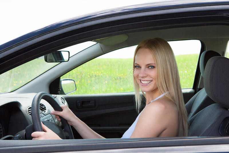 驾驶汽车的愉快的年轻美丽的妇女 免版税库存图片