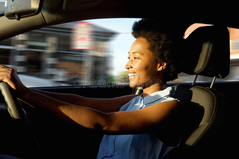 驾驶汽车的愉快的年轻非洲妇女 库存图片