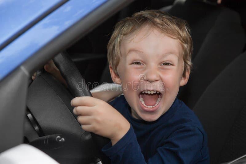驾驶汽车的男孩 免版税库存照片