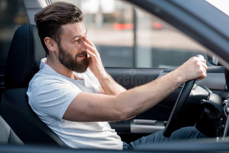 驾驶汽车的疲乏的人 免版税库存图片