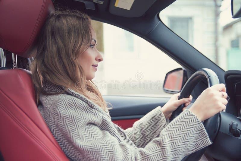 驾驶汽车的确信的成功的妇女 免版税库存图片