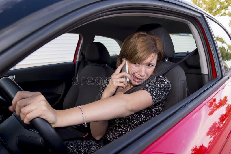驾驶汽车的美丽的妇女,当发短信使用手机分散了时 库存照片