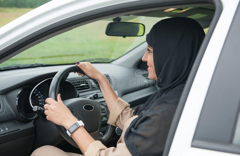 驾驶汽车的美丽的阿拉伯回教妇女 免版税库存照片