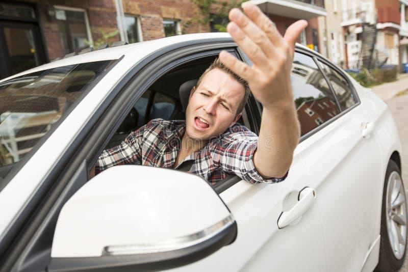驾驶汽车的被激怒的年轻人 被激怒的司机 图库摄影