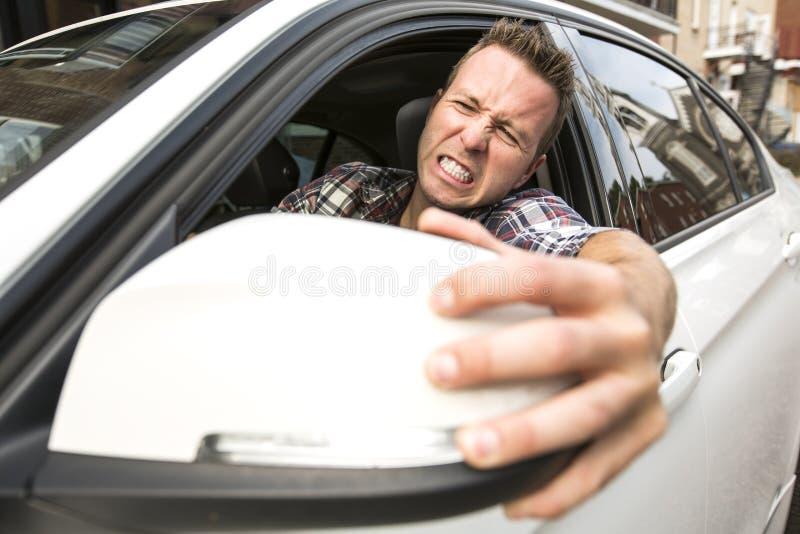 驾驶汽车的被激怒的年轻人 被激怒的司机 免版税库存照片