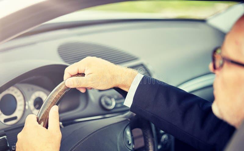 驾驶汽车的资深商人手 库存照片