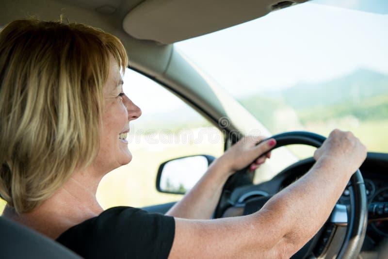 驾驶汽车的高级妇女 免版税库存照片