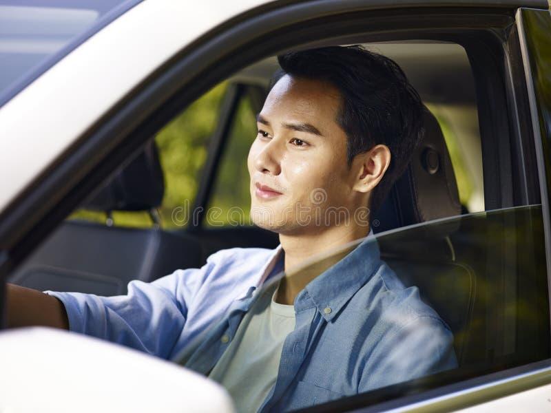驾驶汽车的年轻亚裔人 免版税库存图片