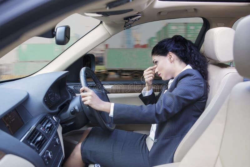 驾驶汽车的头昏眼花的印地安女实业家 库存照片
