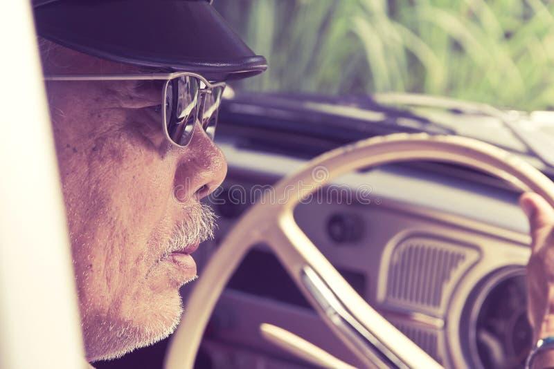 驾驶汽车的更老的人 免版税库存图片