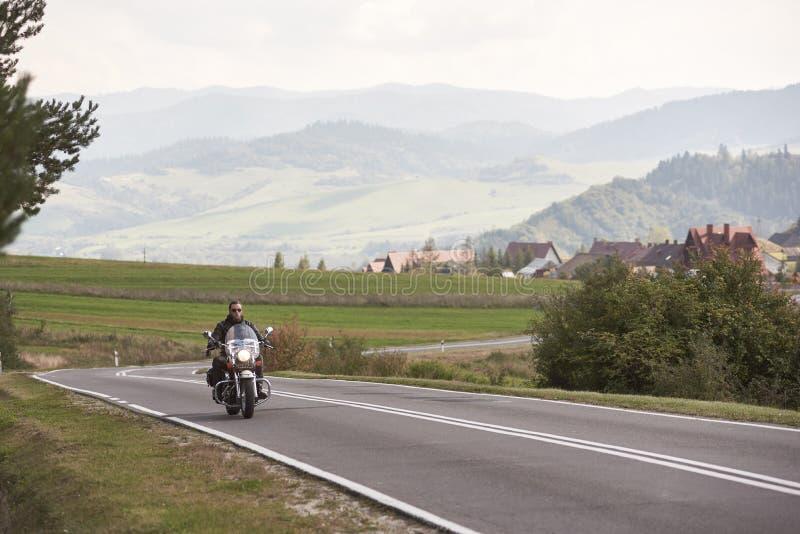 驾驶沿晴朗的路的黑皮革成套装备的骑自行车的人现代强有力的摩托车在夏日 库存图片