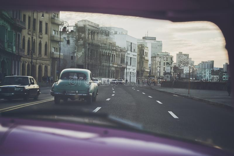 驾驶沿Malecà ³ n在日落在哈瓦那,古巴 库存照片