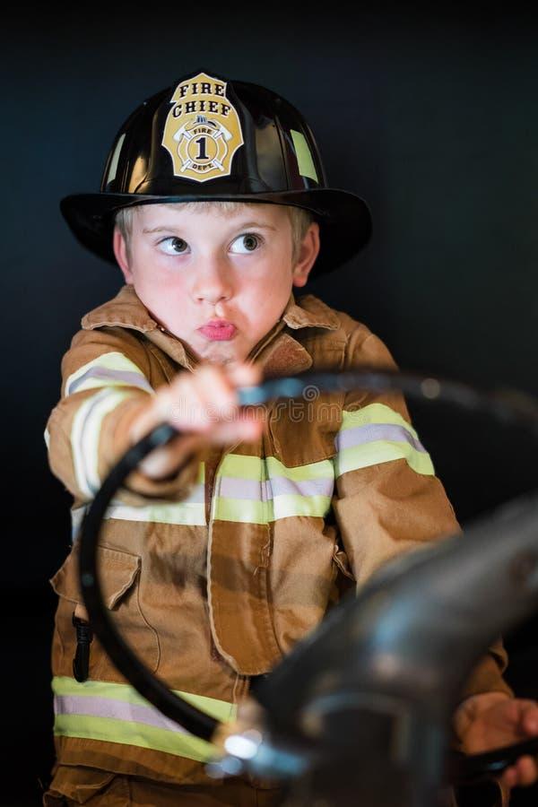驾驶消防车的男孩 免版税库存图片