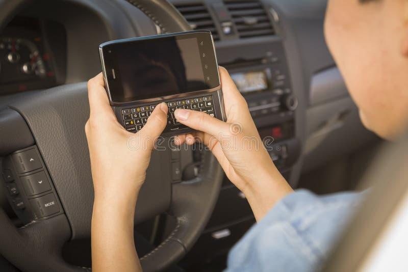 驾驶混合的族种的妇女发短信和 库存图片