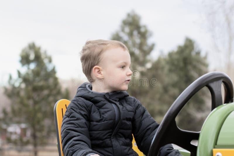 驾驶玩具拖拉机的四岁的小孩在都市室外农场 图库摄影