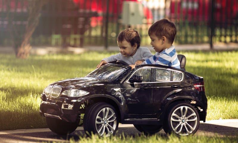 驾驶玩具汽车的小男孩和女孩在公园 库存照片