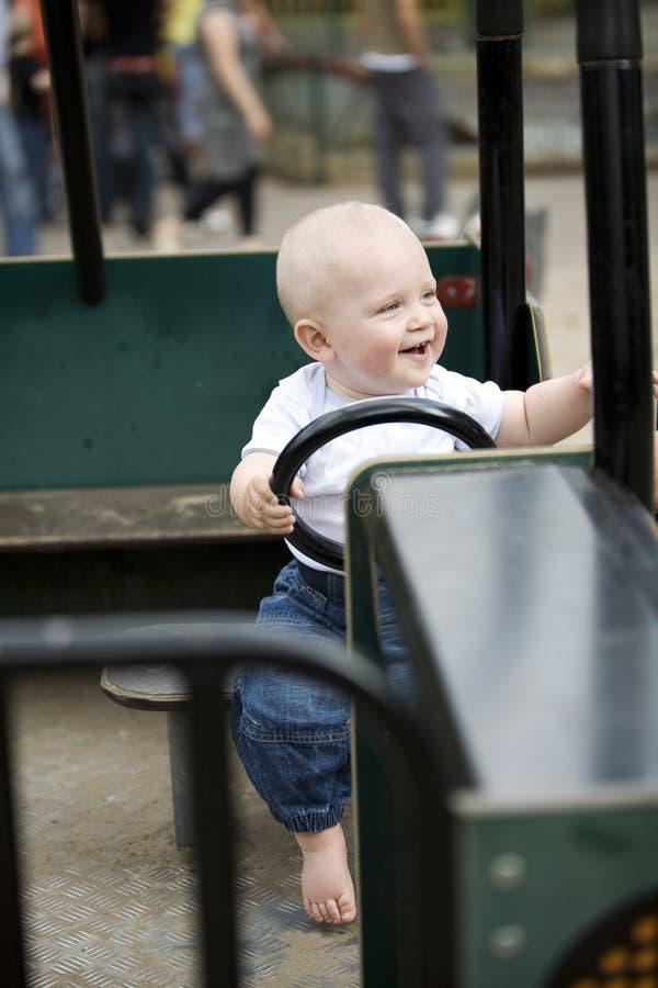 驾驶玩具汽车的白肤金发的男孩 免版税库存图片