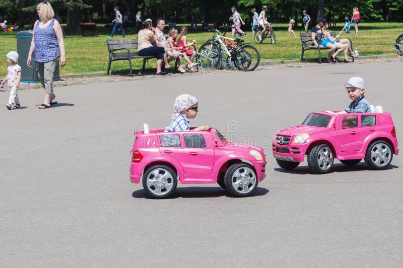 驾驶玩具电车的两个小男孩在公园 免版税库存图片