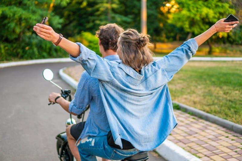 驾驶电自行车的可爱的年轻夫妇在夏天期间 免版税库存照片