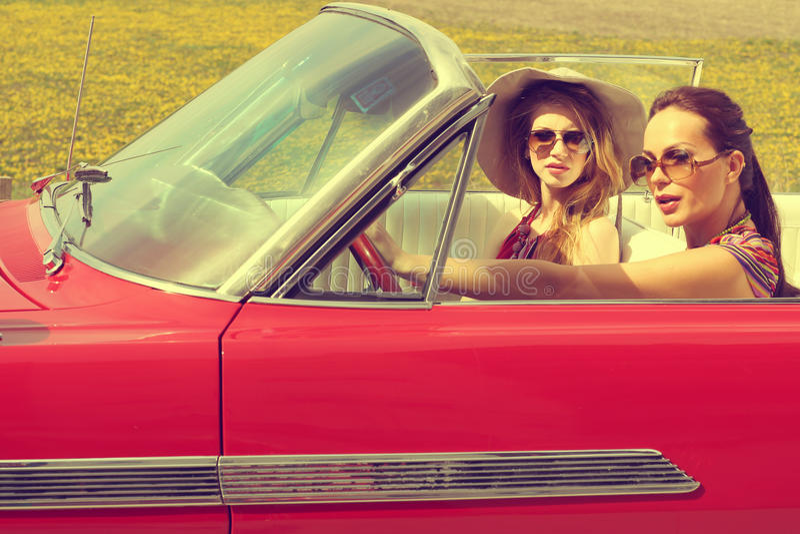驾驶红色汽车减速火箭的葡萄酒佩带的accesoriess的美丽的妇女 免版税库存照片