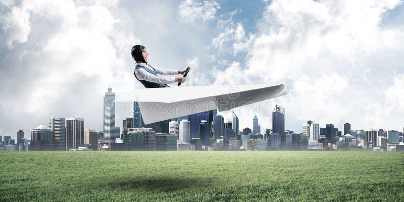 驾驶纸飞机的愉快的飞行员 免版税库存图片