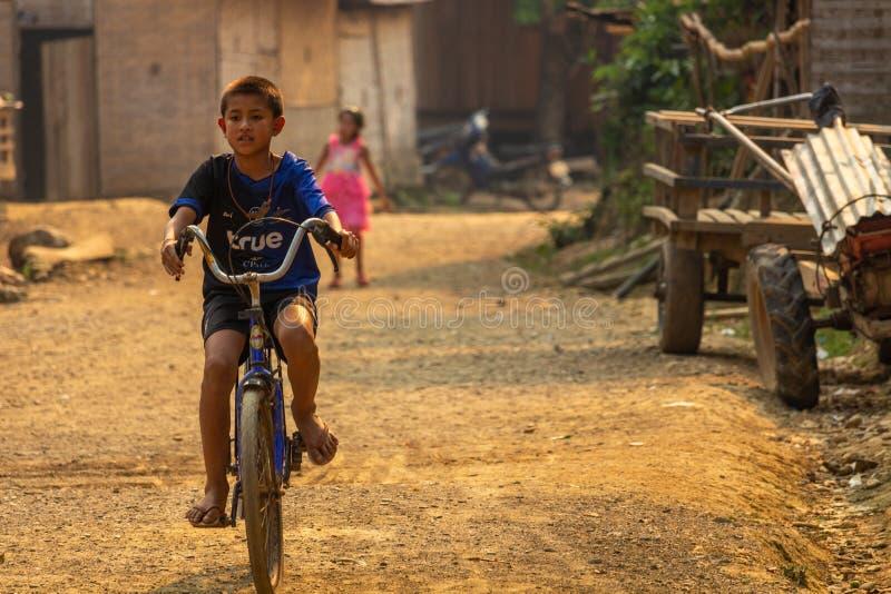 驾驶自行车老挝的村庄孩子 图库摄影