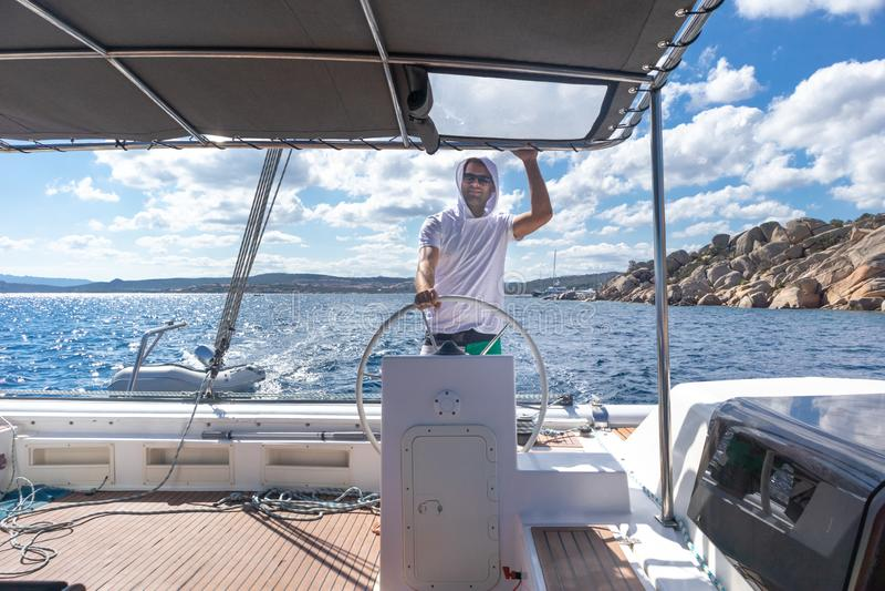 驾驶花梢筏风船的可爱的男性船长在镇静蓝色海水的晴朗的夏日 免版税库存照片