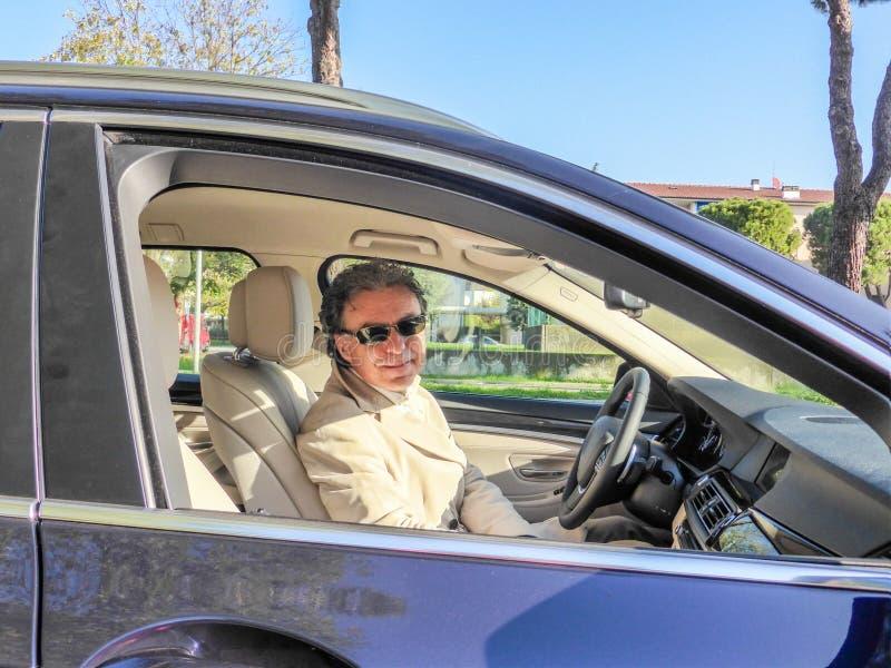 驾驶豪华蓝色汽车的典雅的中年人 免版税库存图片