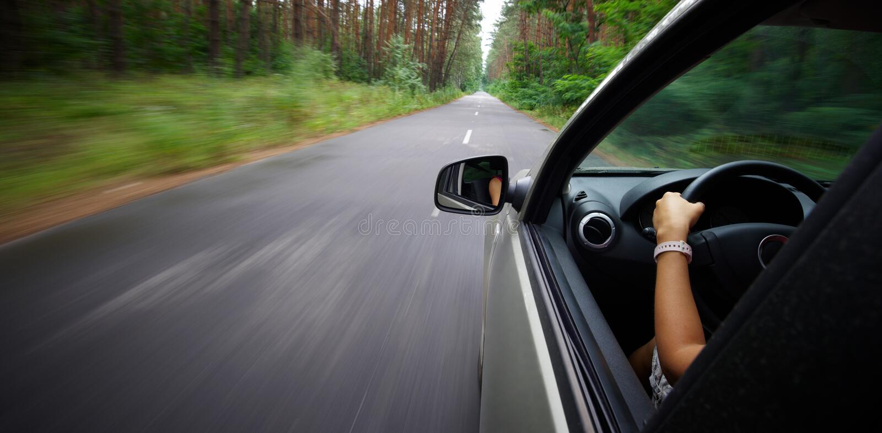 驾驶车的背面图的年轻美丽的妇女 免版税库存图片