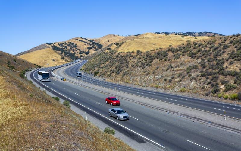 驾驶通过加利福尼亚金黄小山;圣路易斯水库状态度假区标志和水坝在右边 免版税库存图片
