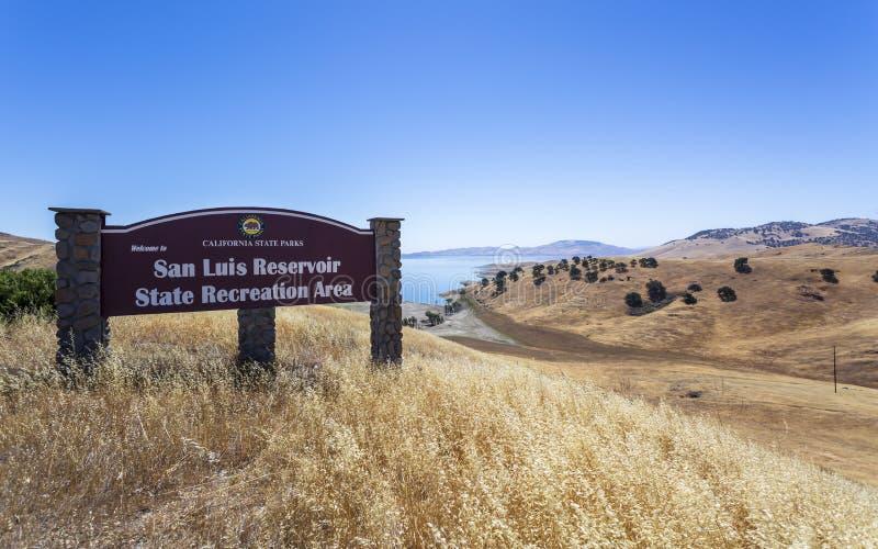 驾驶通过加利福尼亚金黄小山;圣路易斯水库状态度假区标志和水坝在右边 库存照片