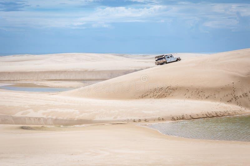 驾驶通过独特的白色沙丘,在它附近的有些水池的卡车在Lencois Maranhenses在北部巴西 免版税库存照片