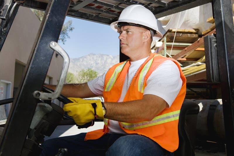 驾驶铲车的确信的工作者在工作场所 免版税库存照片
