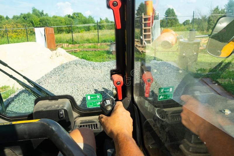 驾驶铲车 卡车的小室通过操作员的眼睛 一辆铲车的工作在建造场所的 库存图片