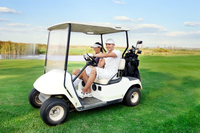 驾驶高尔夫球推车的愉快的夫妇 免版税库存图片