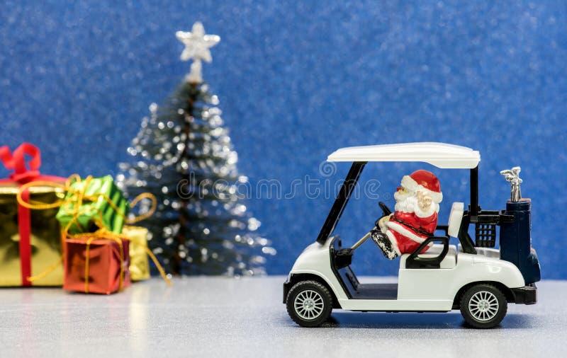驾驶高尔夫球汽车,圣诞晚会的圣诞老人 库存照片