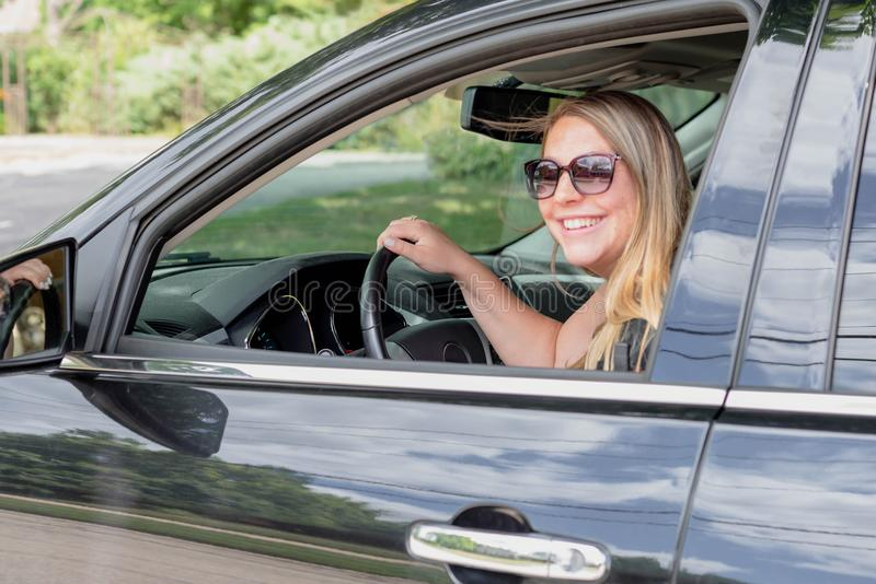 驾驶黑SUV的逗人喜爱的少妇 图库摄影