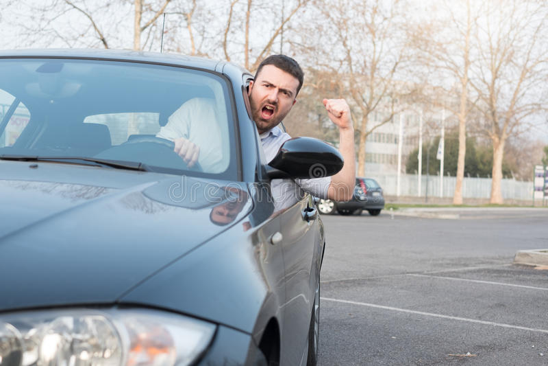 驾驶他汽车和争论的粗鲁的人 免版税图库摄影